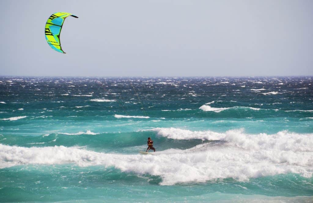 A man kiteboarding on his own over waves on a turquoise sea, in the daytime.