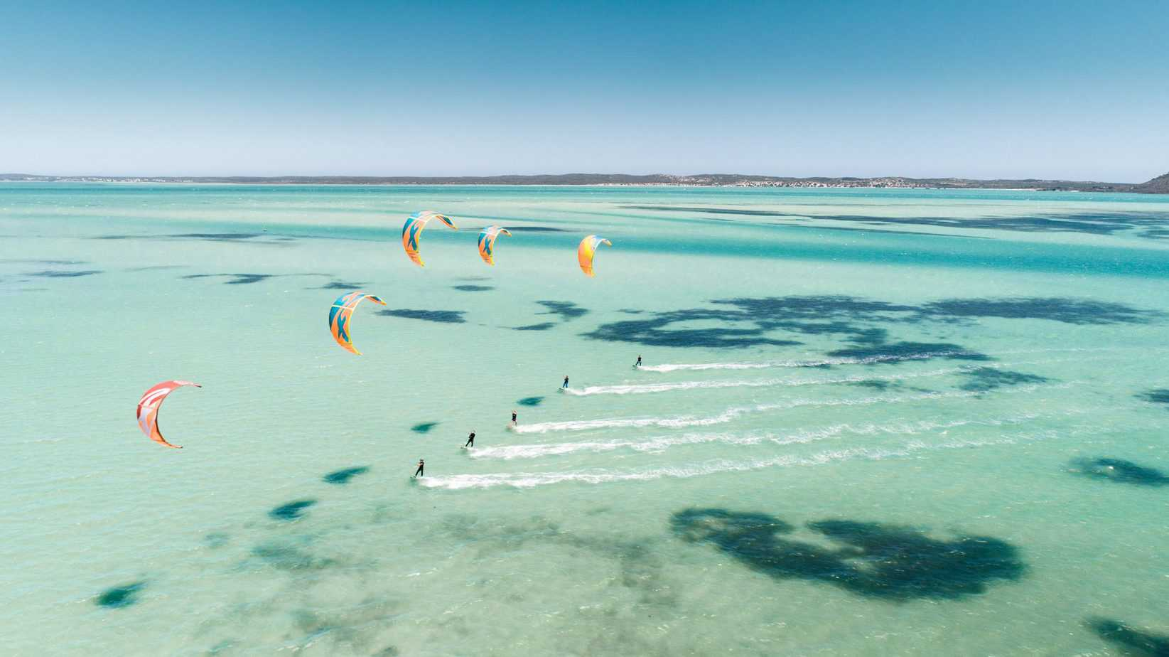 Several kiteboarders riding in the same direction on turquoise sea, in the daytime.